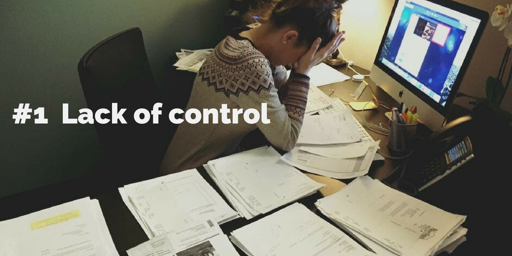 1-Lack of control. A woman buries her face in her hands at work, in front of stacks of paper.