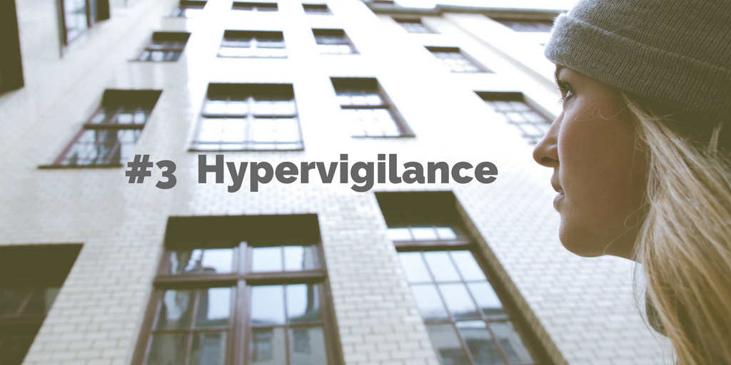 3-Hypervigilance. A woman looks nervously up at a wall of windows.