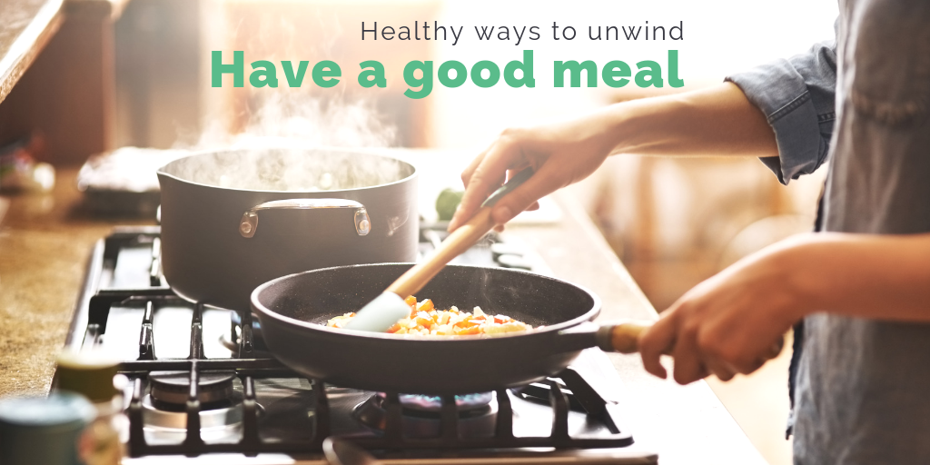 """Healthy ways to unwind: Have a good meal"". Someone tending to a pan on a stove while steam rises from a pot."