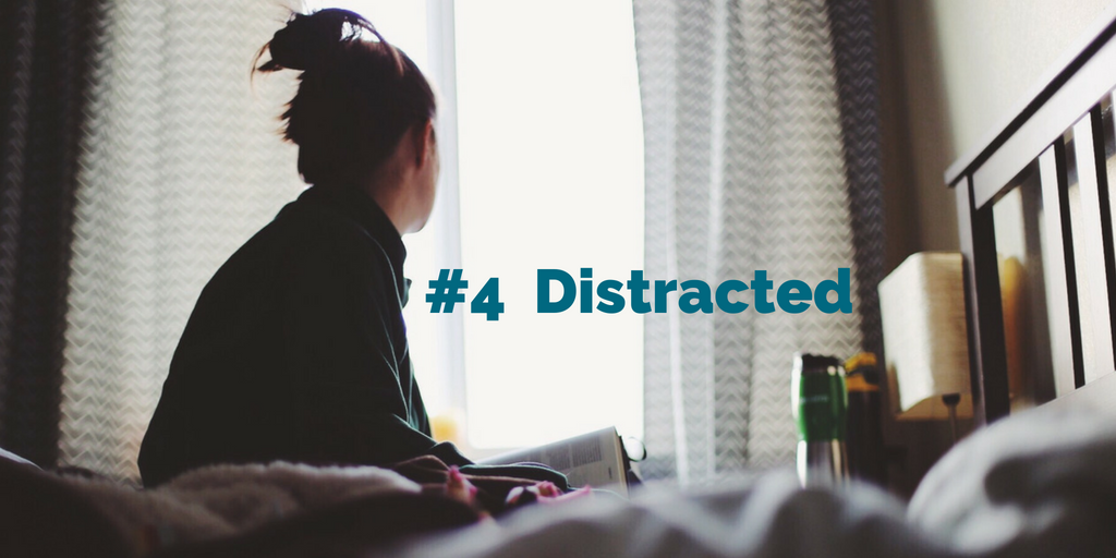 #4 Distracted. A young woman sitting on a bed with a book in her lap gazes out a brightly lit window.