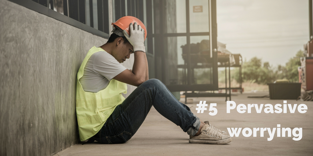 5-Pervasive worrying. A construction worker sits against a wall, holding his head and staring forward.