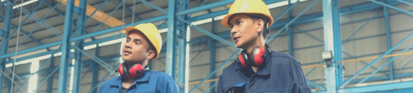 Two men in hardhats chatting in an industrial warehouse.