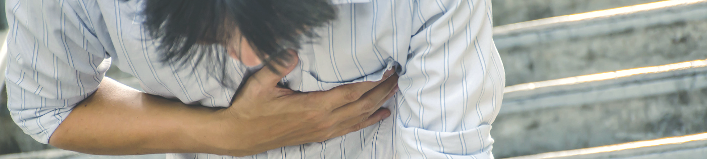 A man bent over, clutching his chest while having a panic attack.